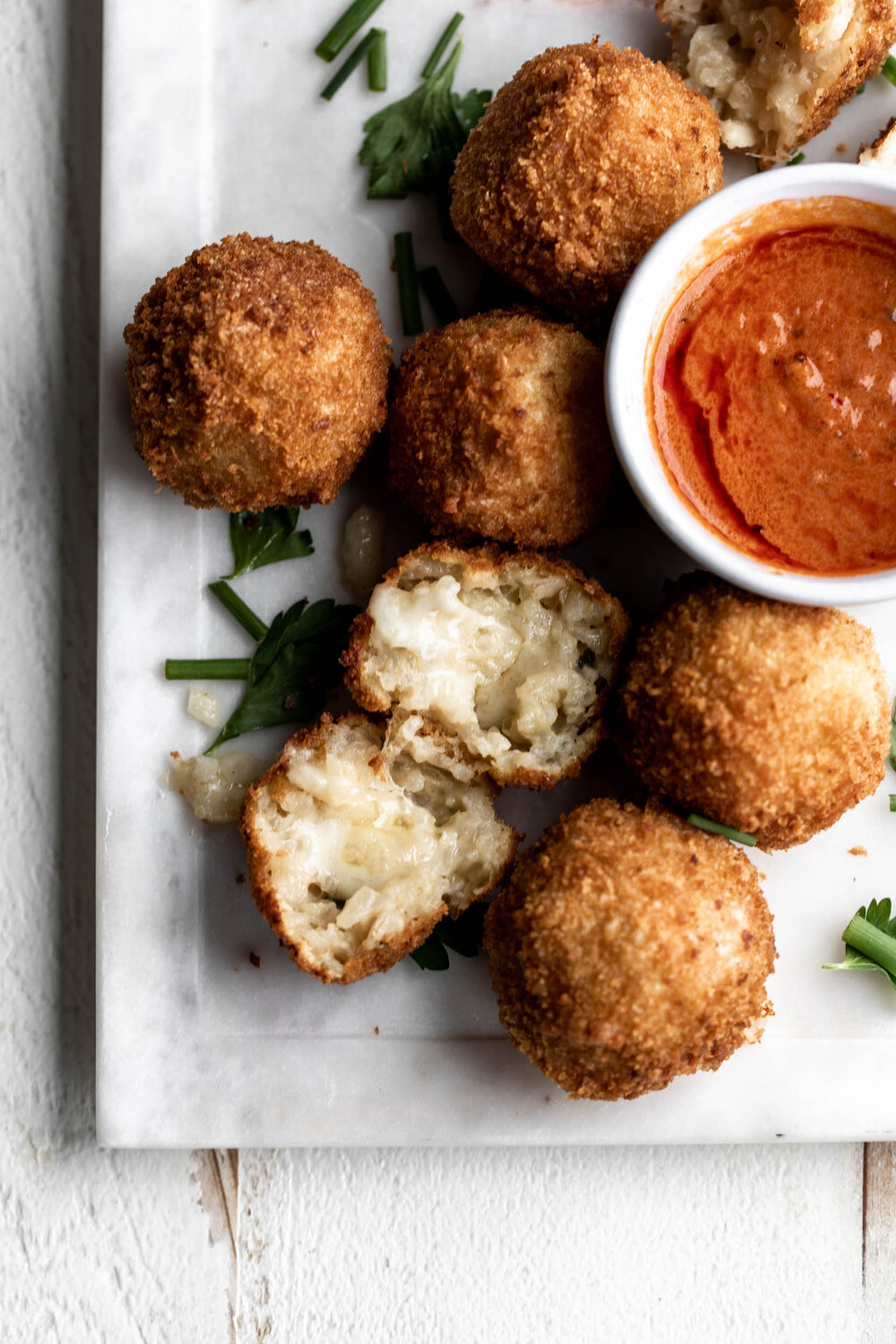 Crispy fried risotto balls stuffed with cheese and paired with spicy creamy marinara make a great appetizer for any occasion.