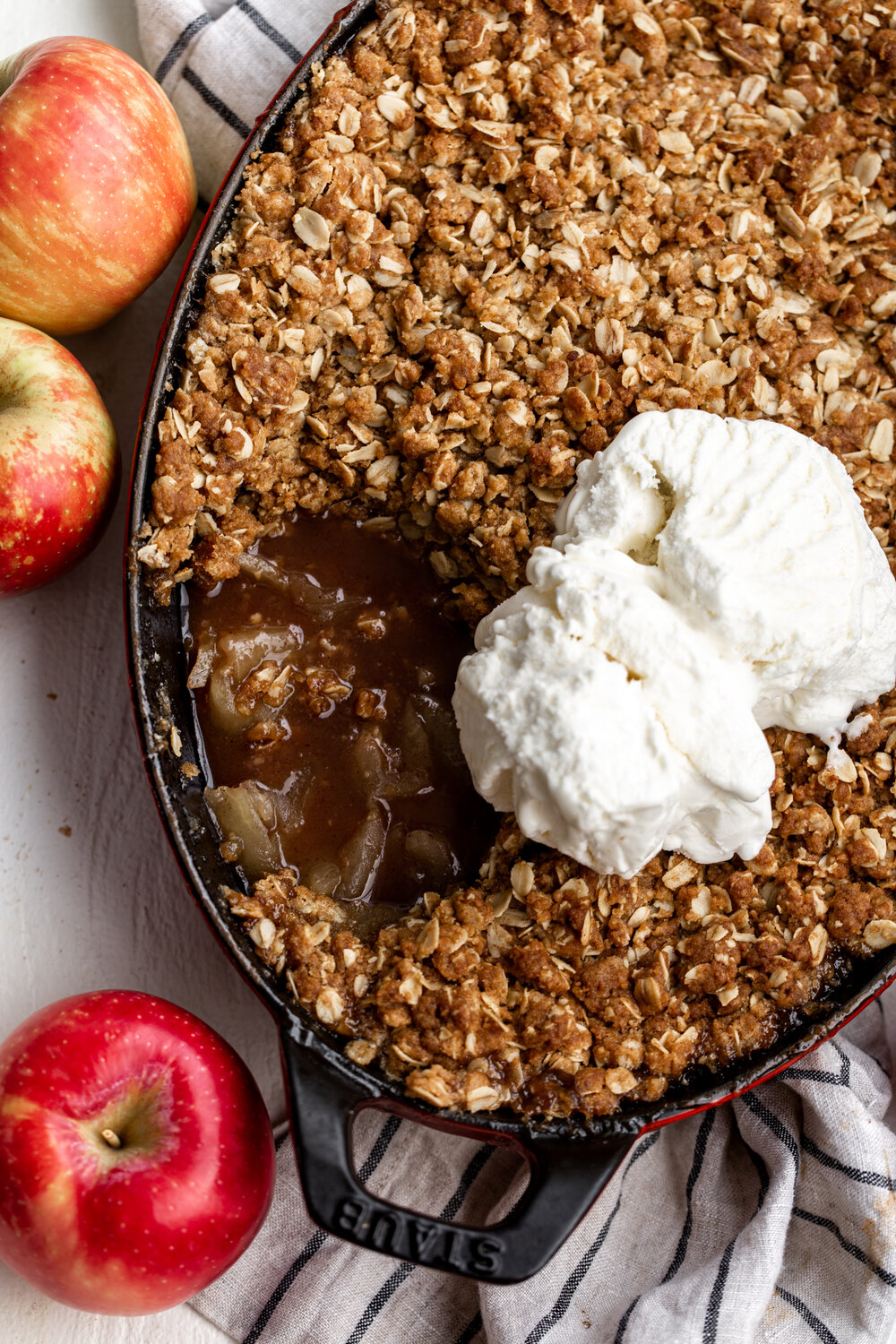 Apple crisp made with sliced honeycrisp apples tossed in cinnamon sugar topped with a crumbly, oat topping. golden brown on top with a scoop of vanilla ice cream and whole apples on the side