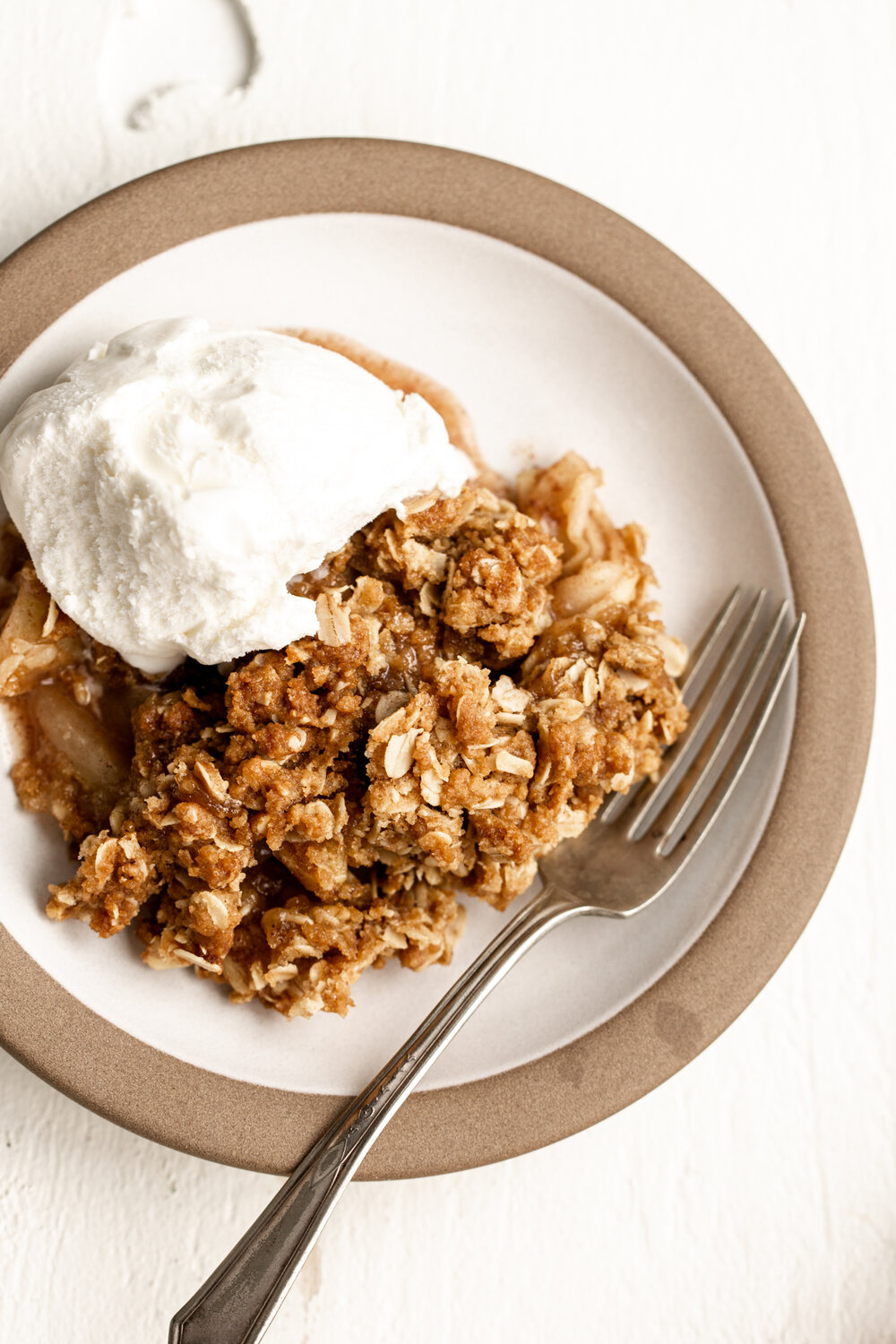 scoop of apple crisp fall dessert on a small plate with oat mixture topped with vanilla ice cream