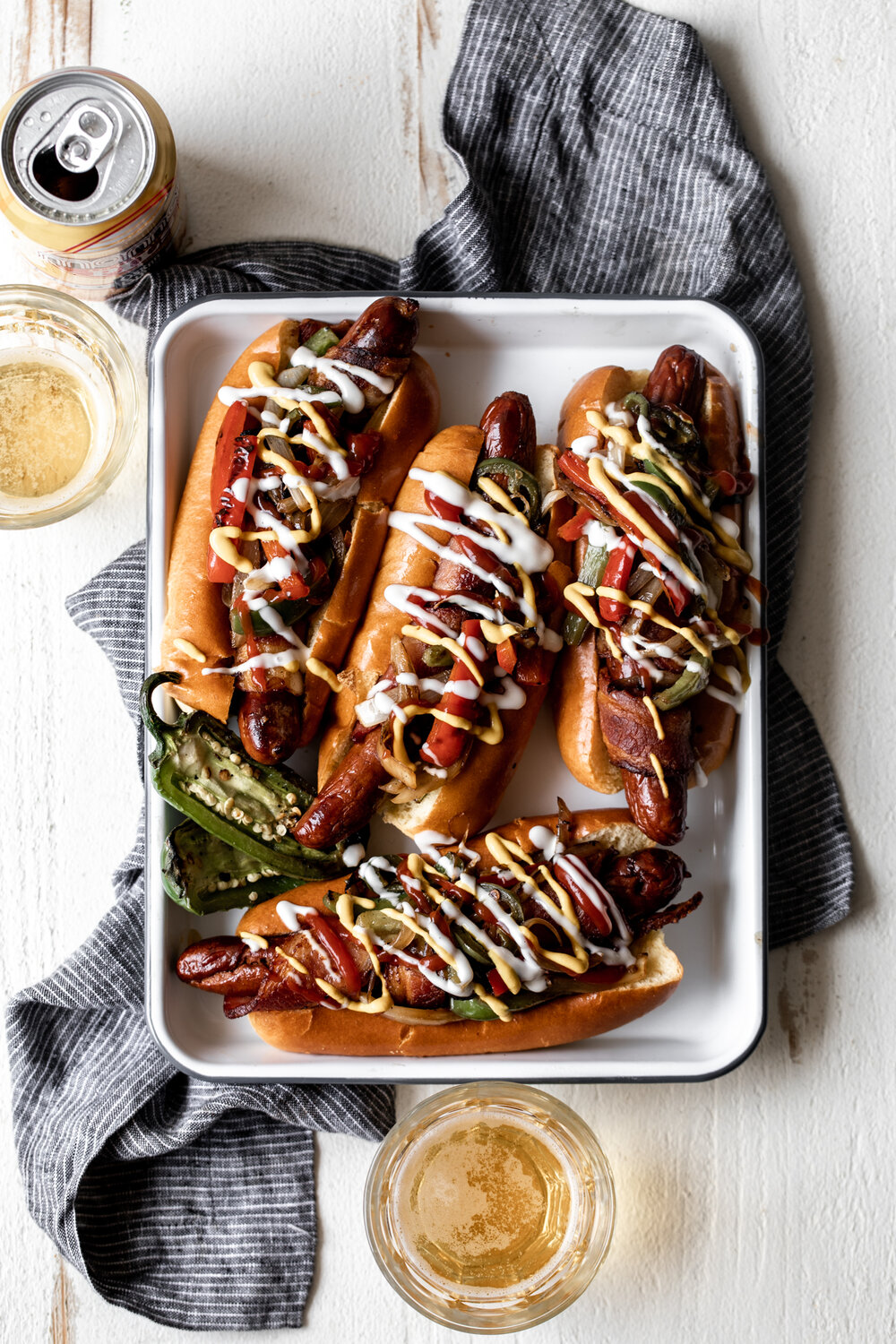 Bacon wrapped hot dogs topped with sautéed peppers, onions and jalapeño for an at home version of an LA street food favorite danger dogs