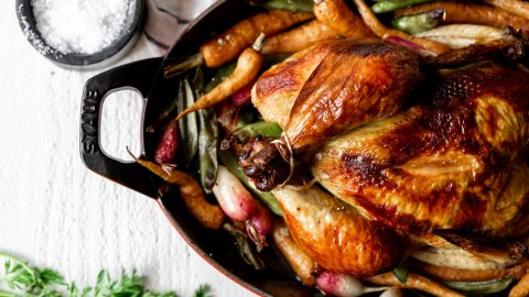 roasted chicken in a red baking dish overhead shot with peas and carrots