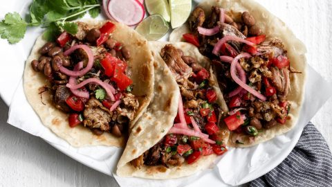 shredded pork carnitas on flour tortillas with pickled onions and tomatoes on a white plate with blue napkin