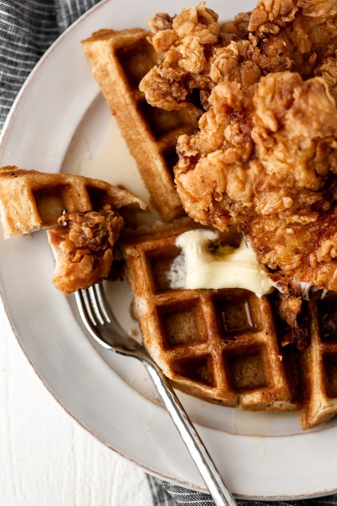 The best fried chicken and waffles recipe for brunch topped with butter and hot sauce maple syrup