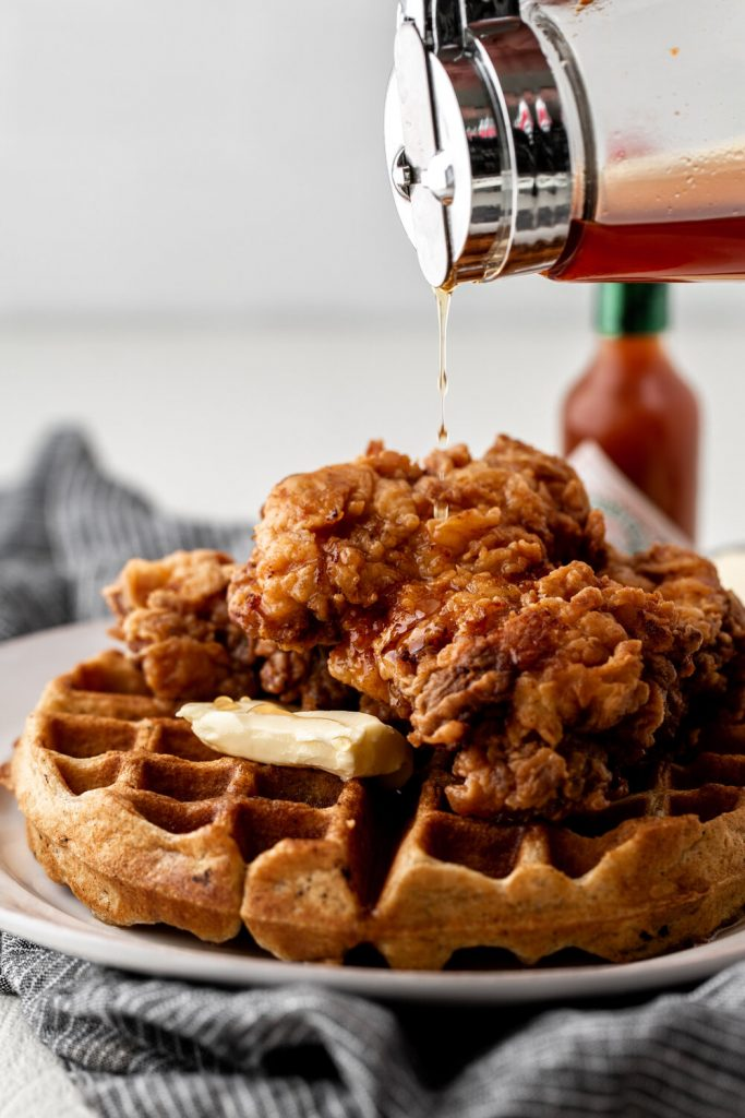 Fried chicken and waffles sweetened with a hint of cinnamon and served with hot sauce maple syrup is the ultimate sweet and savory meal