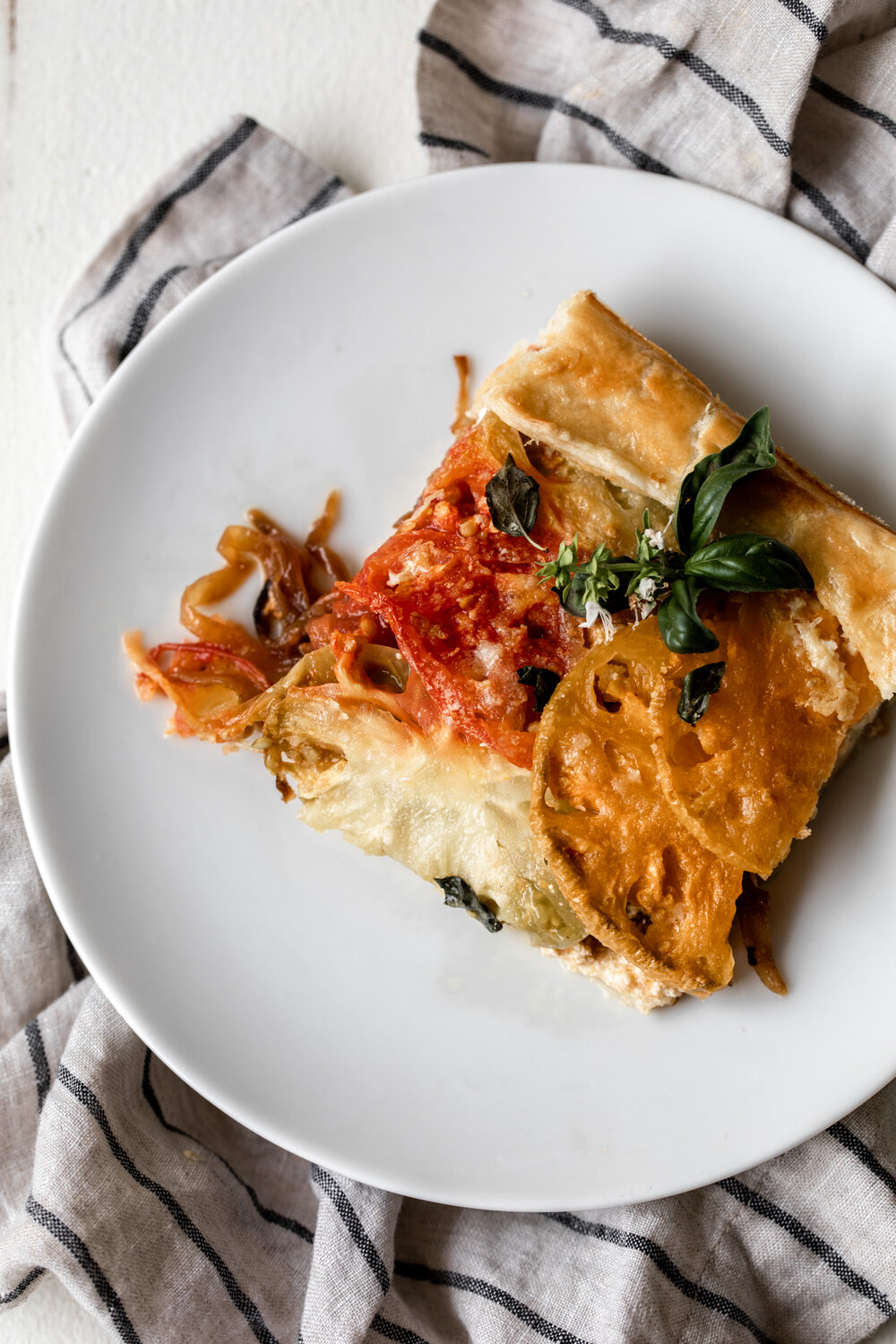 In this tomato galette recipe summer heirloom tomatoes, caramelized onions and ricotta cheese are wrapped in pastry dough for a savory pie