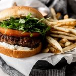 lamb burger with tomato arugula and aioli on a bun with fries