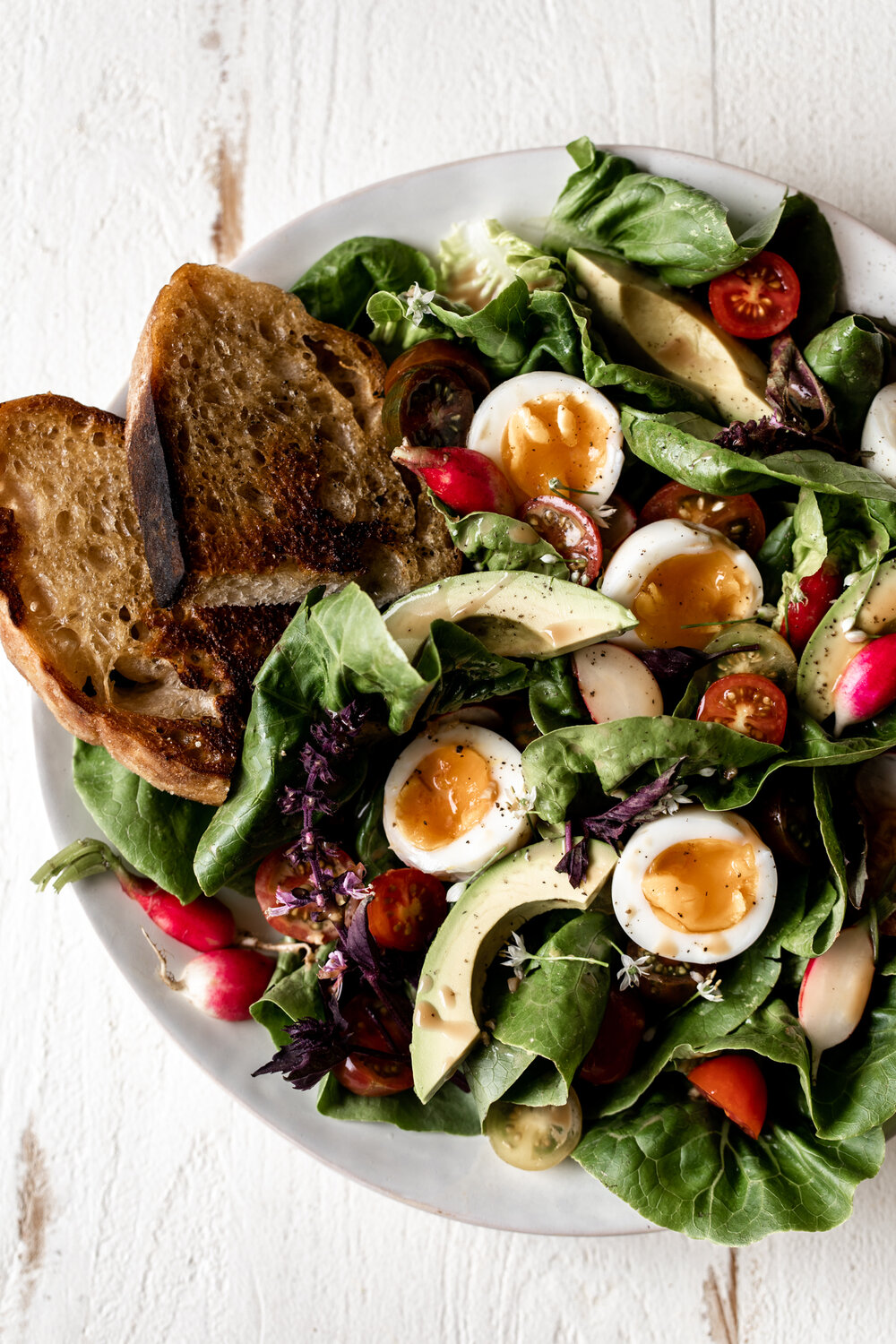 This late summer salad recipe is made with romaine lettuce, cherry tomatoes, avocado, creamy balsamic dressing and jammy soft-boiled eggs.