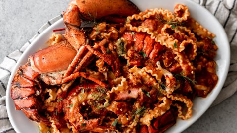 shell on lobster with mafalde pasta noodles in red tomato sauce on a white platter with a white and blue stripe towel