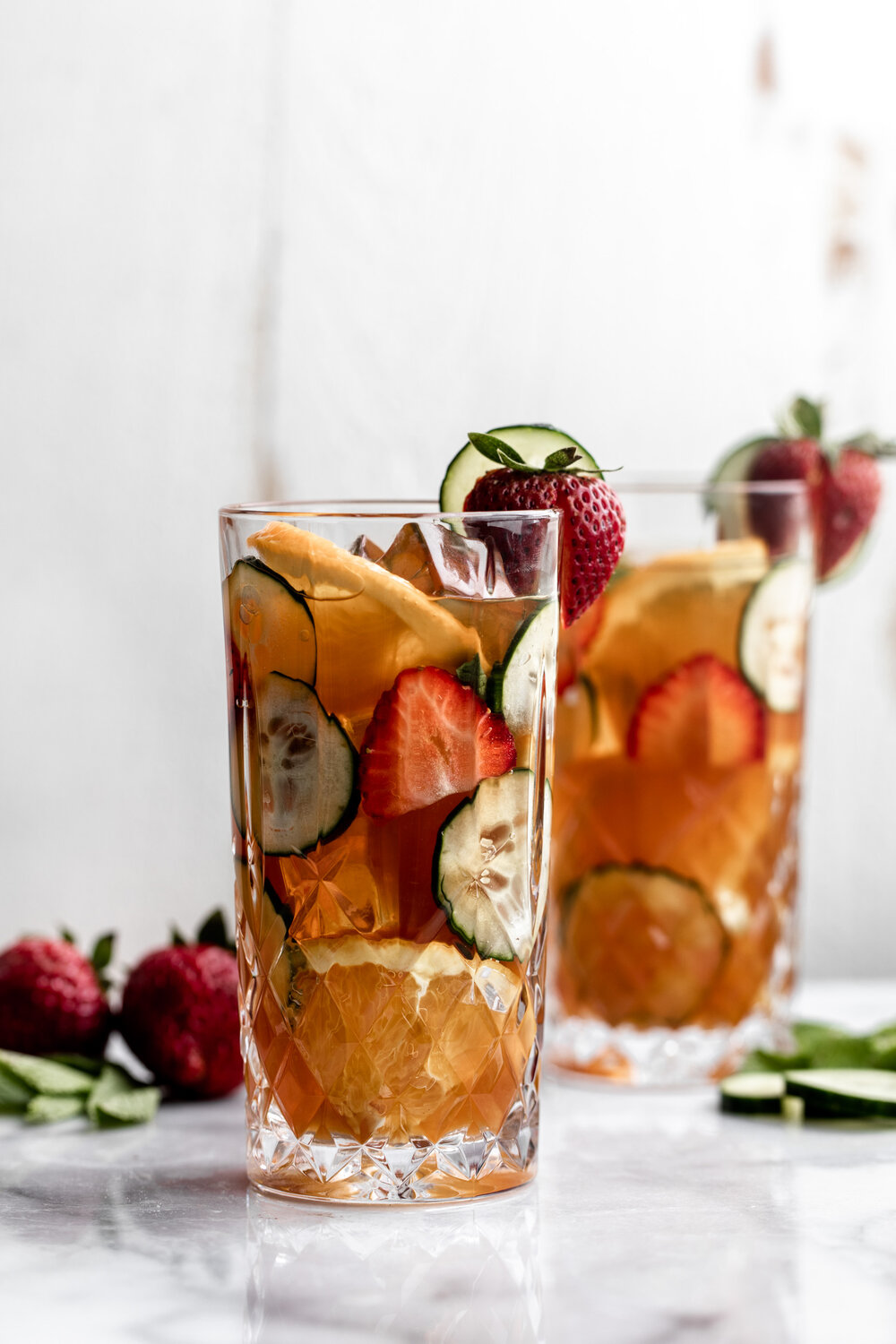 Pimm's Cup with fresh strawberries cucumber and orange slices in a crystal high ball glass