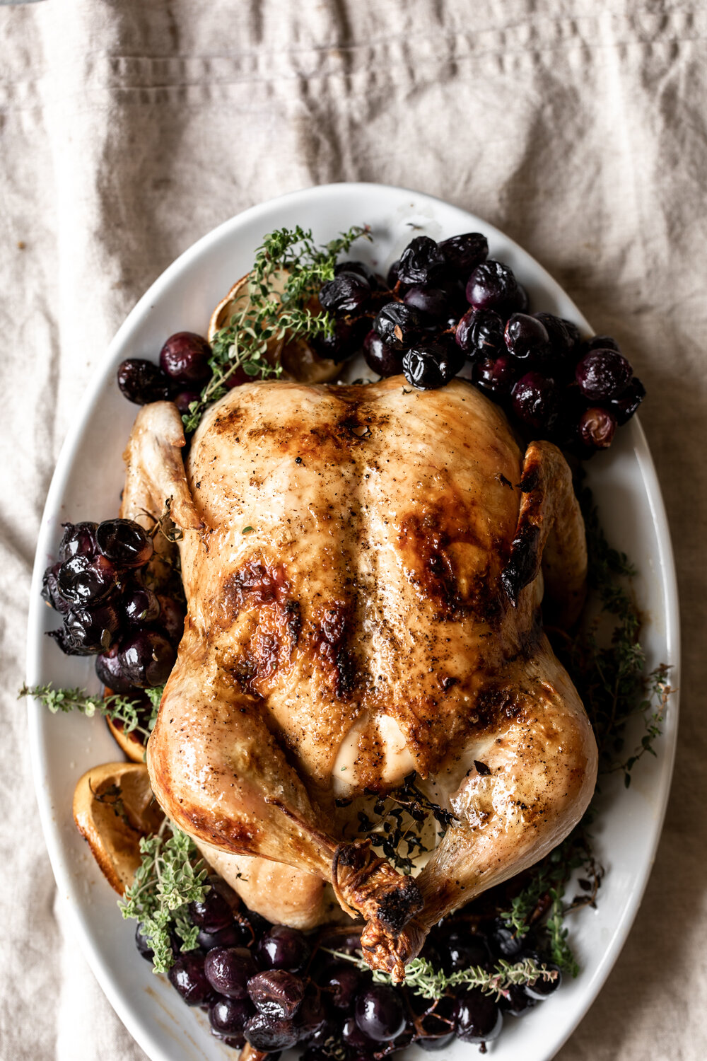 This whole roast chicken is cooked with grapes, thyme and lemon for an easy and impressive seasonal entree.