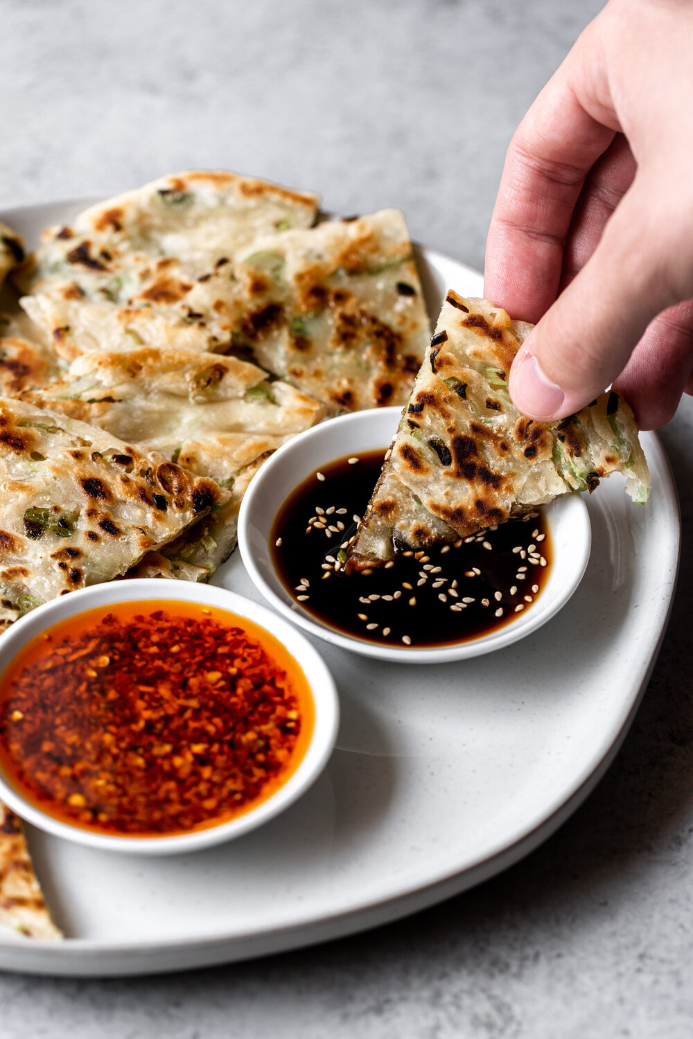 Chinese-style Scallion Pancakes cooked in a skillet dipping piece in Chinese black vinegar
