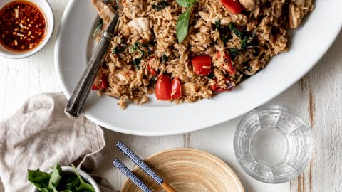 spicy basil fried rice on a white plate with chopsticks