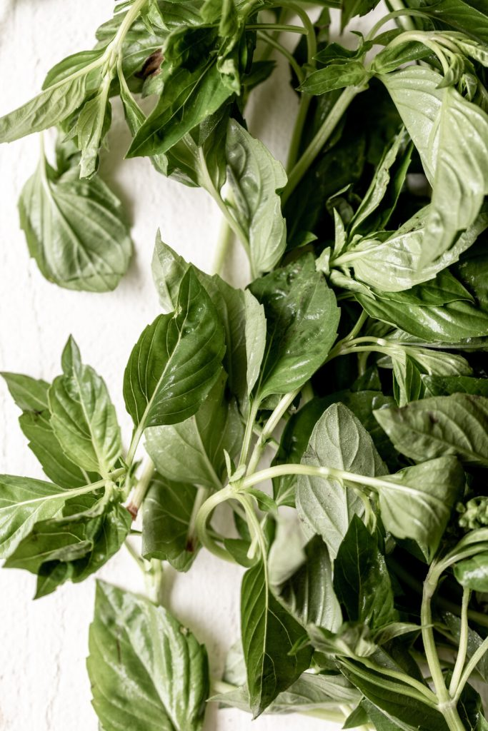 basil leaves on white surface