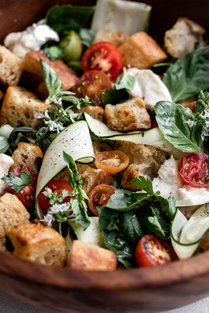 closeup Tuscan-style panzanella salad with tomatoes, zucchini, basil and mozzarella in a wood bowl