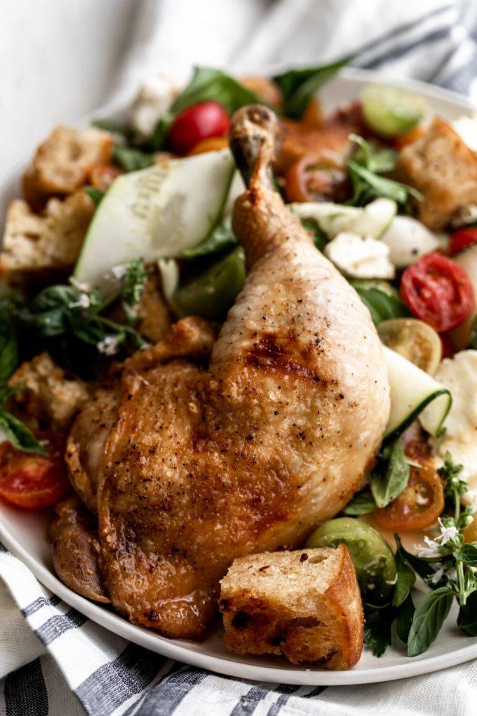 whole roast chicken leg over panzanella salad