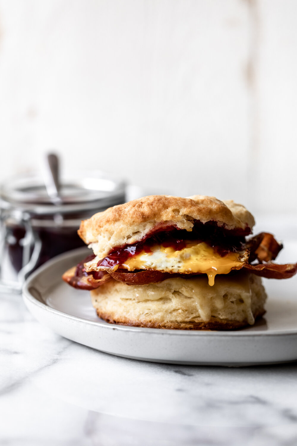 This breakfast sandwich combines both sweet and savory elements with crispy prosciutto, gruyere cheese, jam and a fried egg on a biscuit