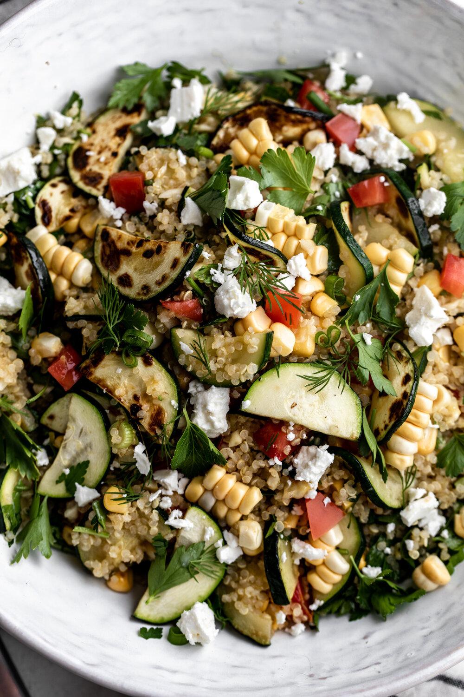 This summer quinoa salad recipe with honey lemon vinaigrette is packed with seasonal ingredients like zucchini, corn, tomatoes in this vegetarian dish.