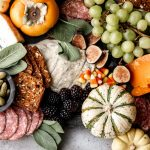 orange and yellow cheeses are served on a grey marble board for a halloween feel with green grapes, mini pumpkins and figs