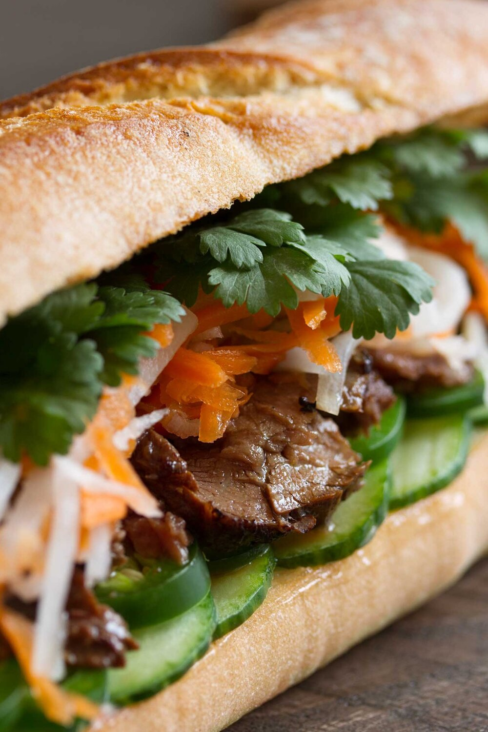 Marinated steak served with pickled vegetables, cilantro and more for a non-traditional version of a Vietnamese banh mi sandwich.