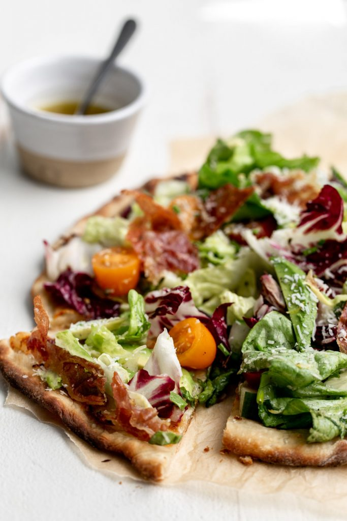 In this East Coast meets West Coast mashup - crispy thin crust pizza is topped with a light salad with avocado and crispy prosciutto.