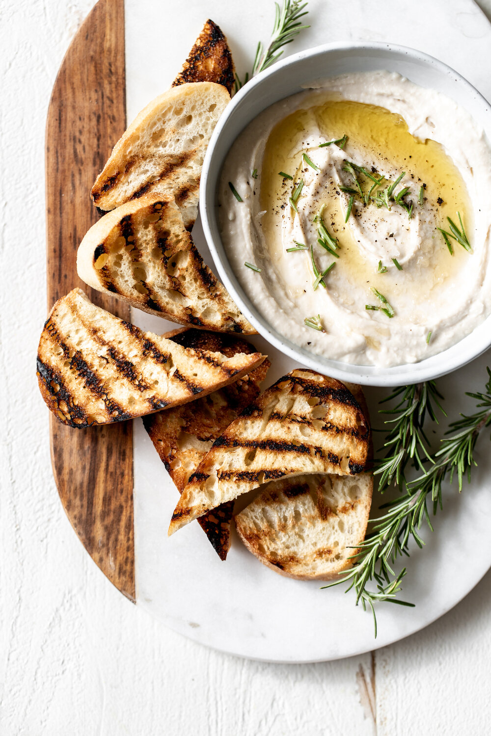 The cannellini white beans blended with oil infused with garlic and rosemary and cheese for an easy Italian bean dip fit for a cocktail party