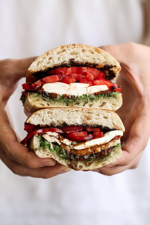Caprese sandwich with ciabatta bread with fresh pesto, sun dried tomatoes, mozzarella cheese, heirloom tomatoes and sweet balsamic glaze.