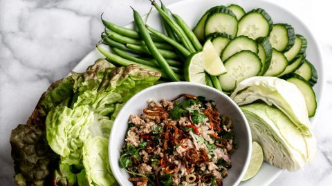 issan style ground pork larb minced pork with herbs arranged on a white platter with cucumber, cabbage and beans
