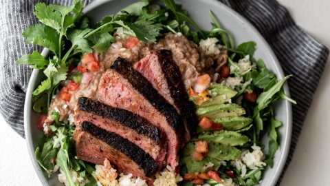 seared sliced steak on top of arugula and crispy rice with avocado and refried beans