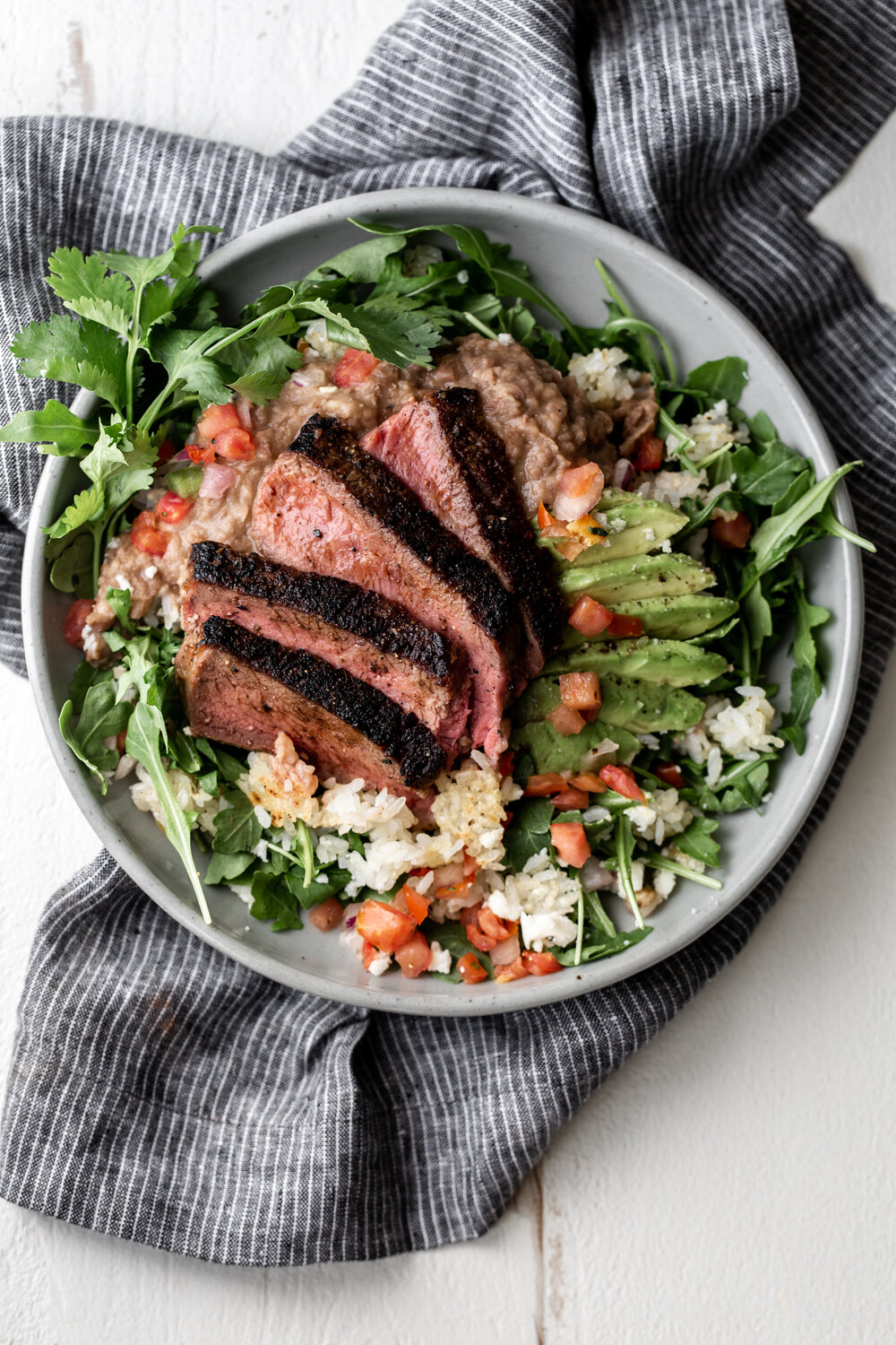 Seared Steak with Refried Pinto Beans, Crispy Rice and Arugula recipe from cooking with cocktail rings