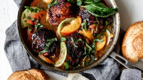 balsamic skin on chicken thighs in a saute pan with peaches and basil