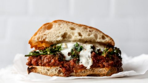 bolognese, rapini and burrata layered onto a ciabatta split bun on a white marble board with subway tile in the background