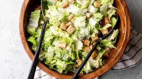 chopped romaine lettuce served with cubed croutons and a light caesar dressing in a wood salad bowl