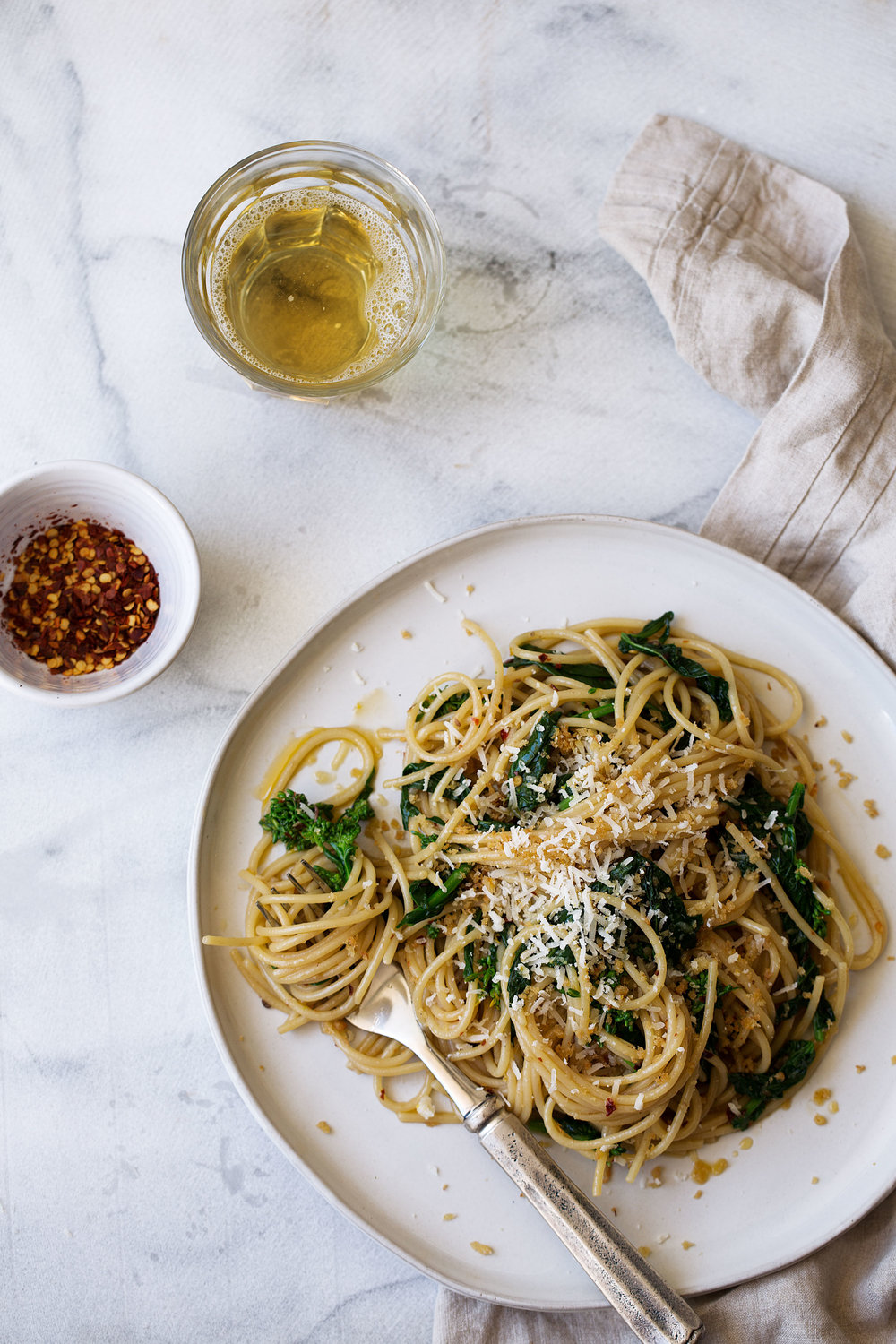 In this rapini pasta recipe spaghetti is tossed with rapini, anchovies & chili oil for an easy twist on aglio e olio and weeknight dinner.