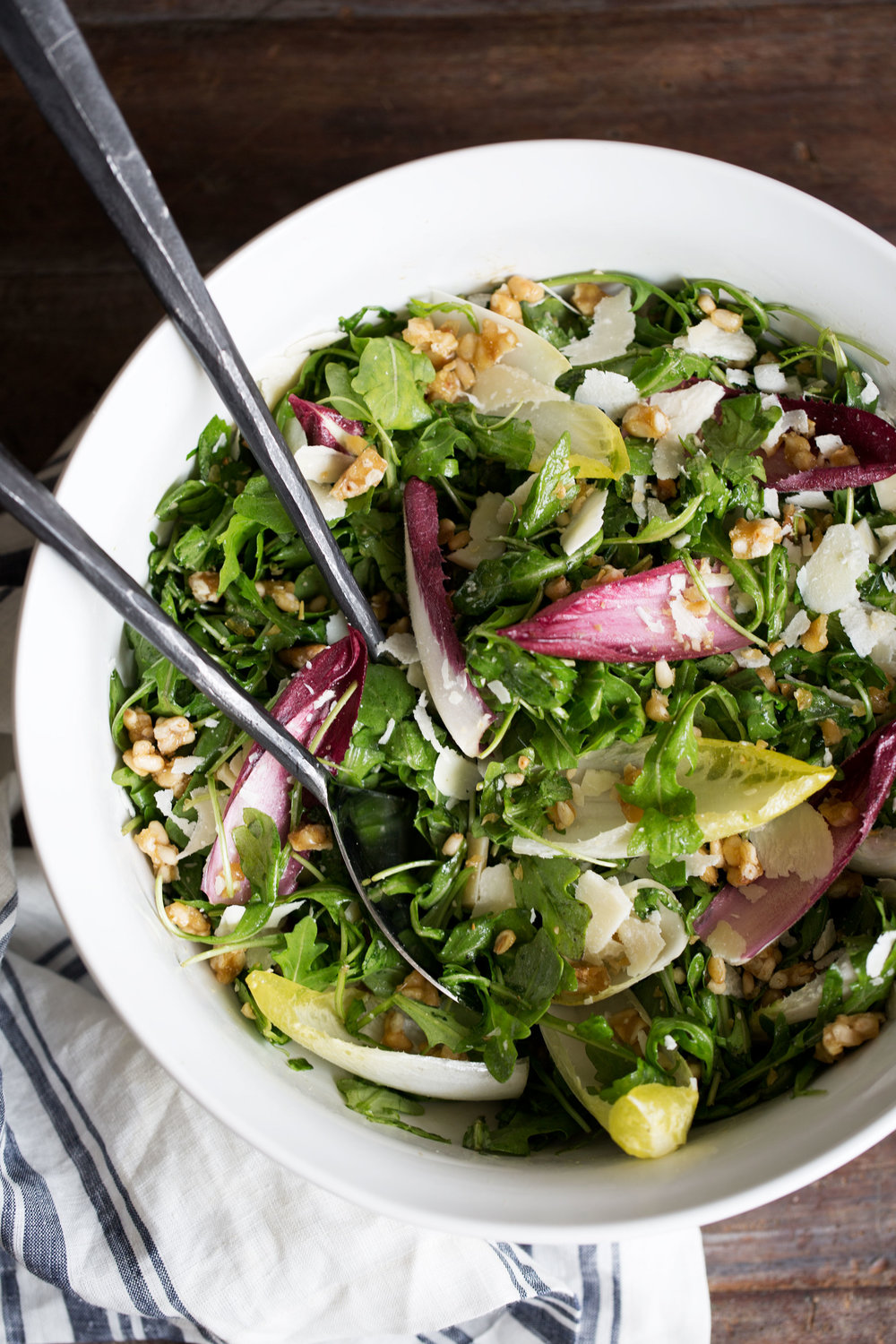 closeup arugula and endive salad with candied pine nuts