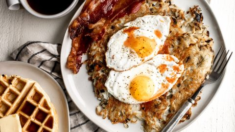 Jalapeno hash browns with eggs on top and bacon on the side