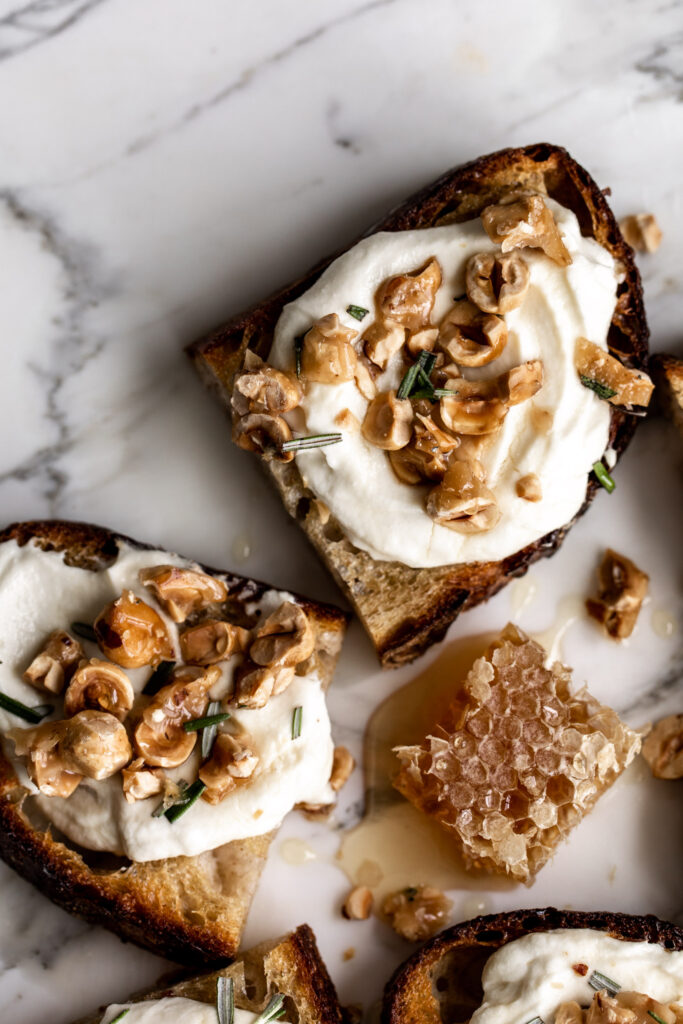 one toasts topped with whipped ricotta, candied hazelnuts and rosemary on a white marble surface with honeycomb