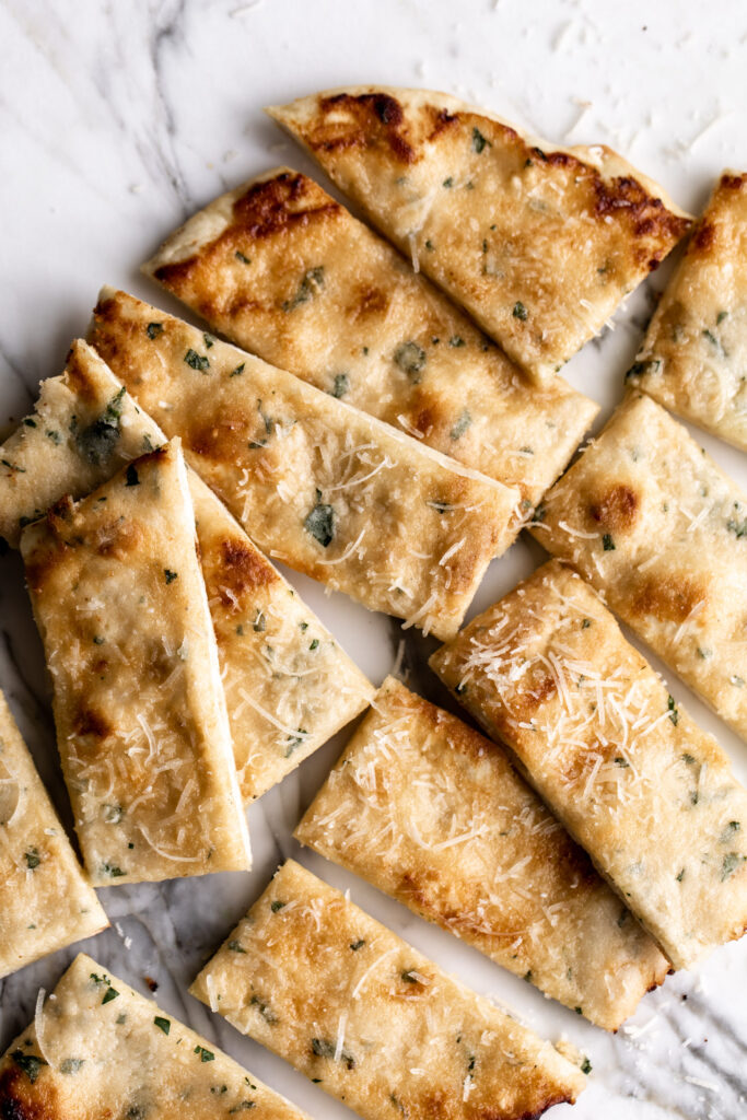 cheesy garlic flatbread with flecks of chopped parsley cut into slices on white marble