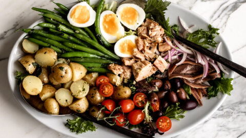 mixed greens, soft boiled eggs, green beans, tomatoes and tuna on a large serving platter for a deconstructed salad