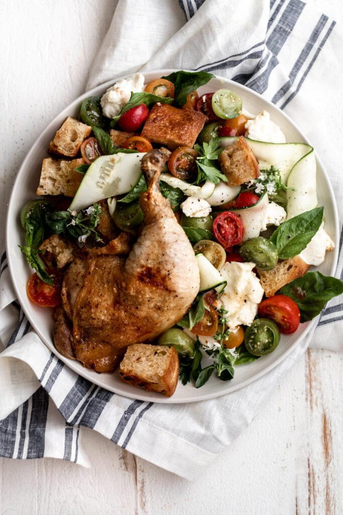 Tuscan-style panzanella salad with tomatoes, zucchini, basil and mozzarella topped with roast chicken leg
