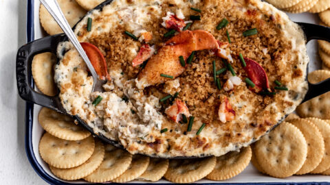creamy baked lobster dip topped with claw meat in a black serving dish