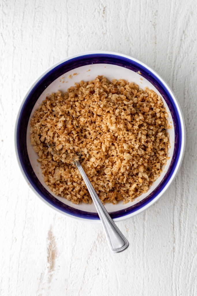 buttered breadcrumbs in a small blue rimmed serving bowl