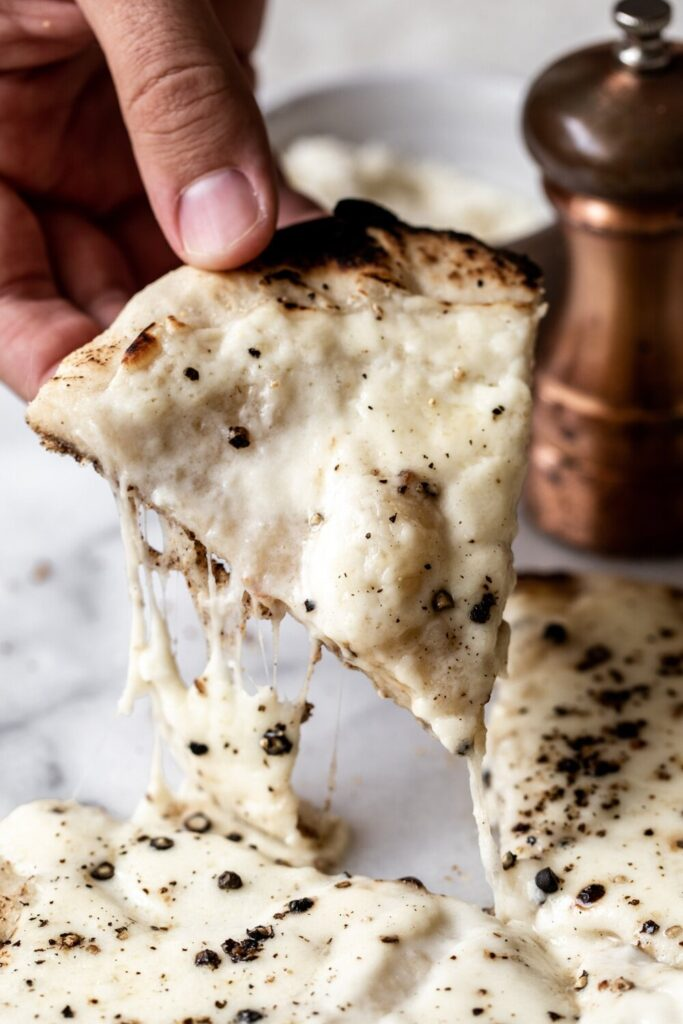 hand holding slice of cacio e pepe pizza | How to Style Food Photos