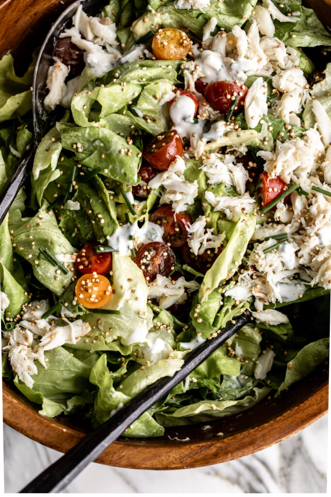 crab salad with avocado, cherry tomato, and puffed quinoa over butter lettuce in a wood bowl