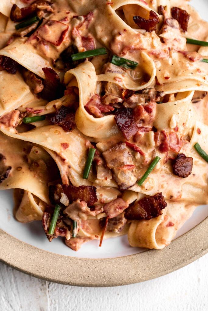 closeup easy creamy tomato and bacon pasta on a ceramic plate