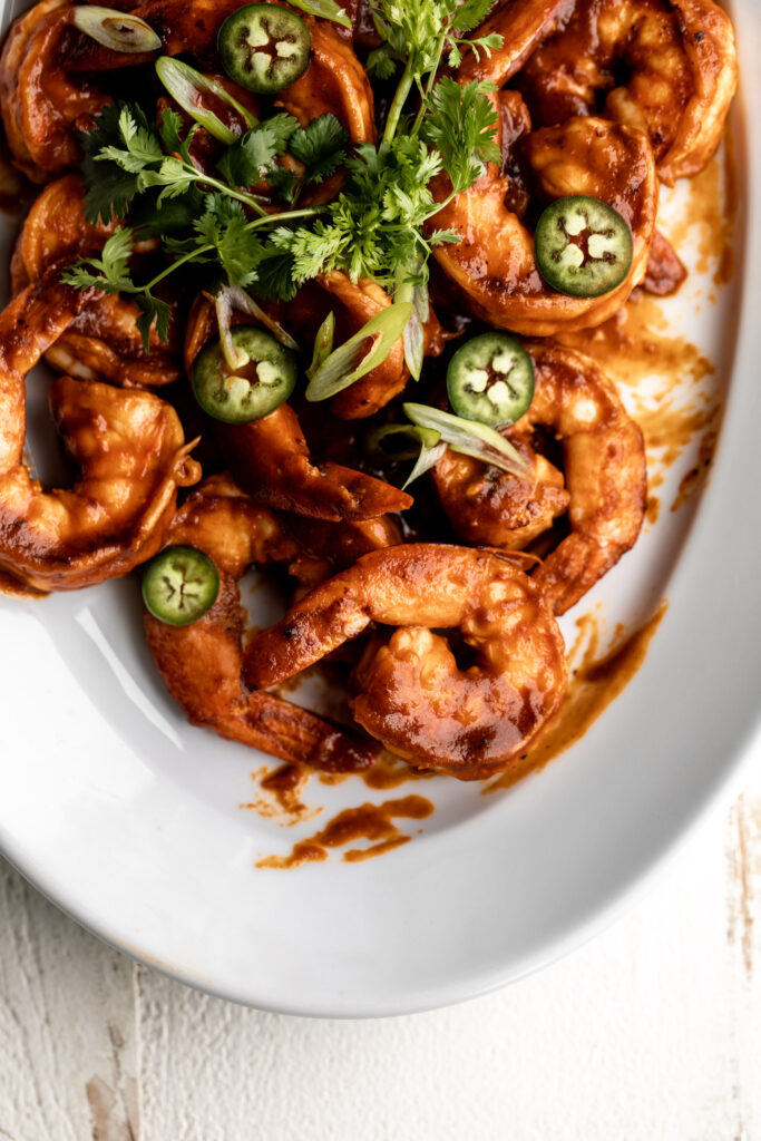 shrimp diablo cooked in a tomato and chili sauce topped with diced green onion and cilantro on a white serving platter
