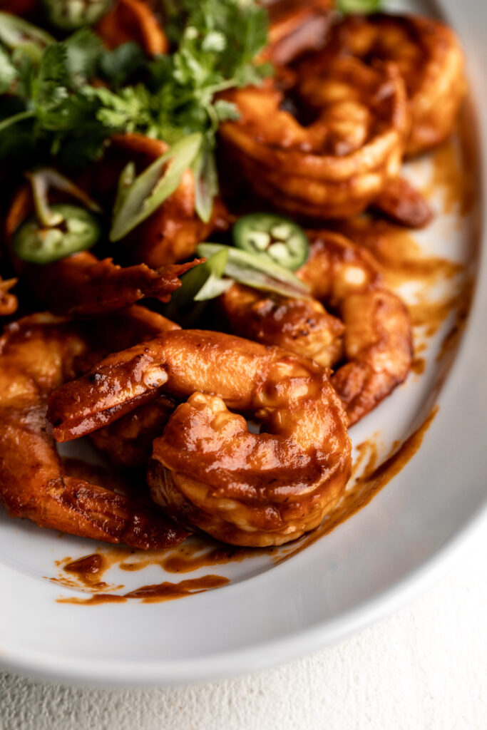 closeup photo of shrimp diablo cooked in a tomato and chili sauce topped with diced green onion and cilantro on a white serving platter