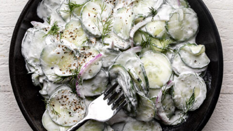 creamy cucumber salad with sour cream sauce, dill and red onion in black stone bowl