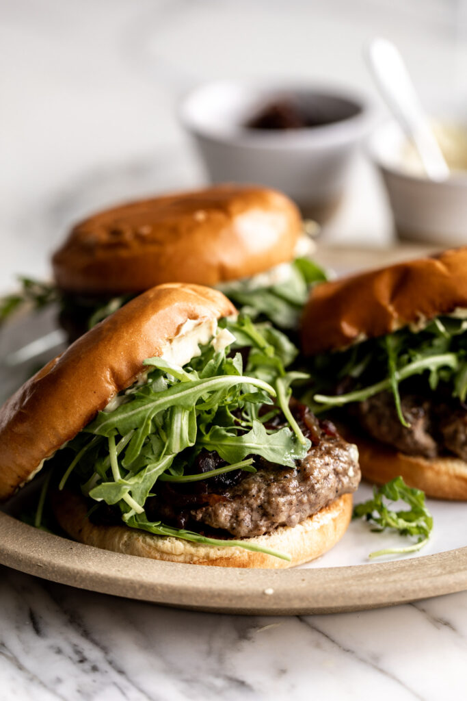 Lamb burgers made using ground New Zealand lamb served on brioche buns with arugula, caramelized onions and homemade curry mayonnaise on a plate
