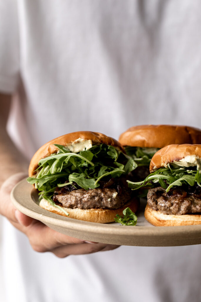 holding plate of lamb burgers made on with caramelized onions, arugula and curry mayo