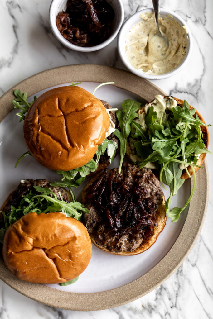 open face lamb burgers made on with caramelized onions, arugula and curry mayo with ingredients on the side